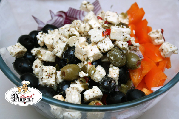Sliced onion, paprika with Feta cheese and black olives in a bowl